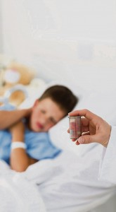 Doctor holding pill bottle with boy in ward